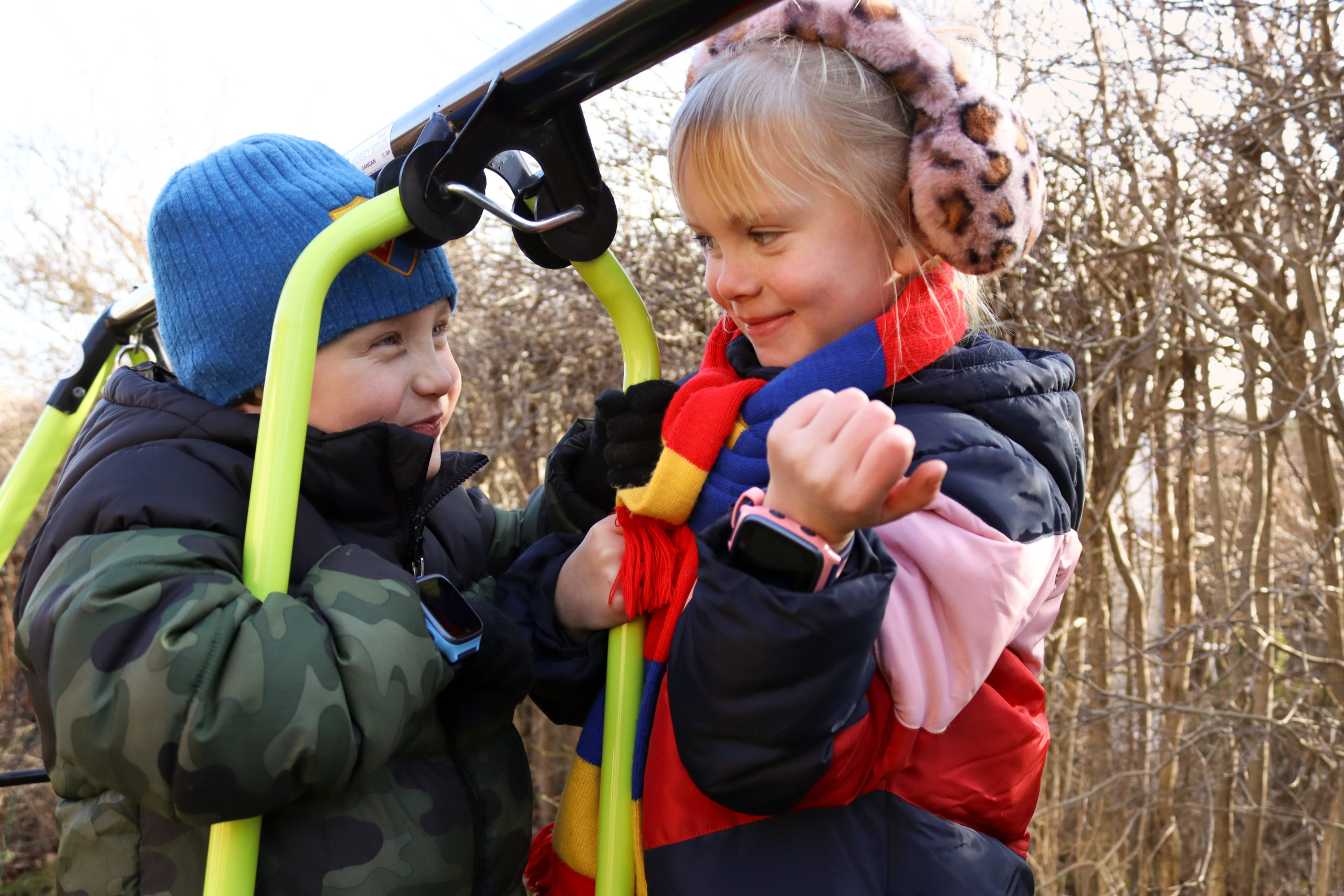 to barn ute på en lekeplass. Jenten til høyre har en rosa xplora klokke, mens gutten til venstre har en blå xplora klokke.