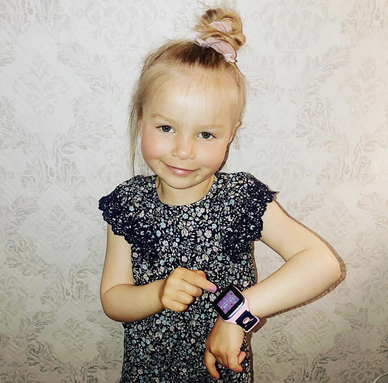 smilende jente som peker på sin rosa xplora klokke.