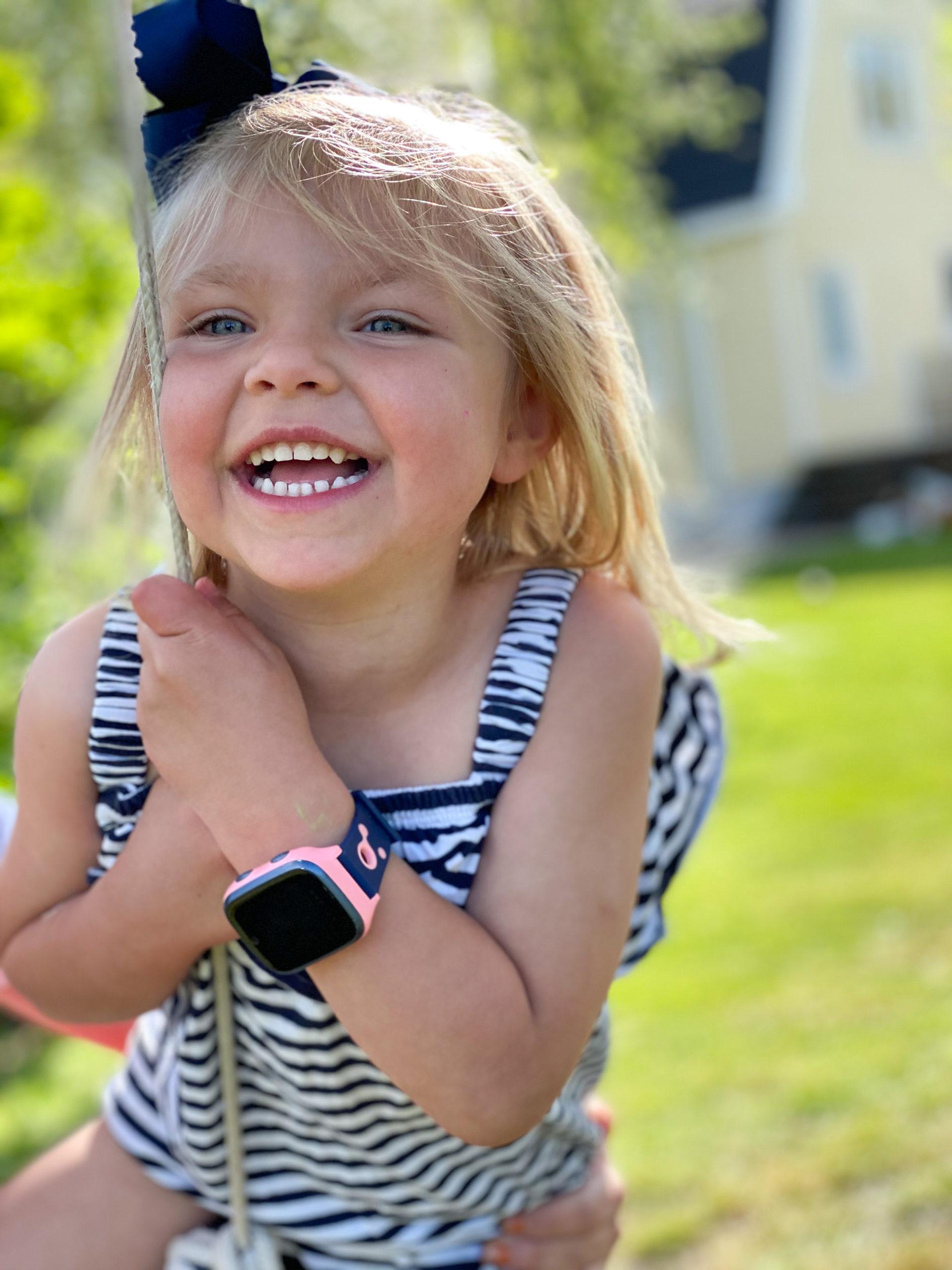 Jente på huske med smartklokke fra Xplora.