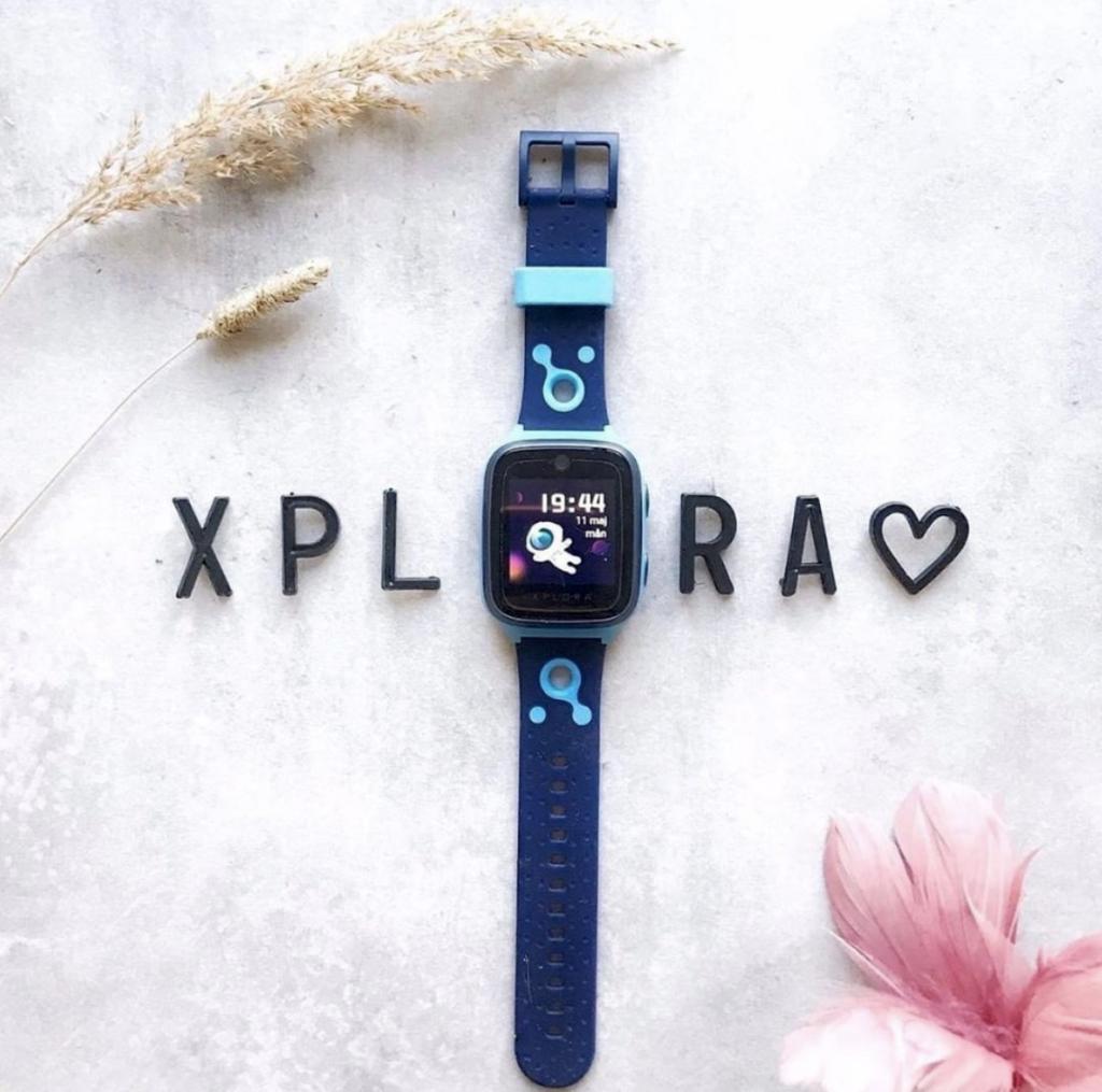 En blå XPLORA telefonklokke ligger på bordet, omringet av teksten XPLORA.