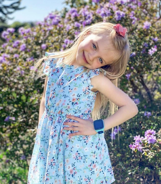 smilende jente med en turkis xplora klokke på venstre arm.