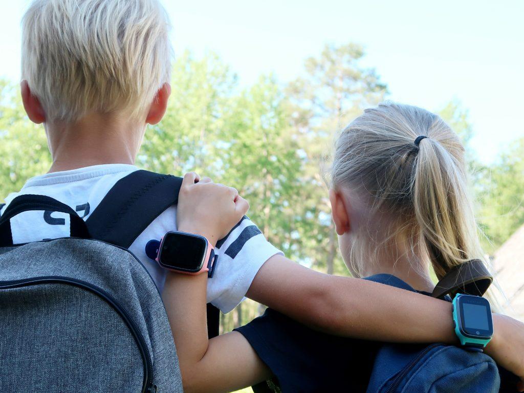 To barn som holder rundt hverandre. Begge har xplora mobilklokke på armen, en i rosa og en turkis.
