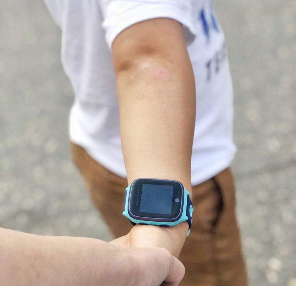 En gutt som holder hånden til sin mor. På armen har han en turkis XPLORA smartklokke