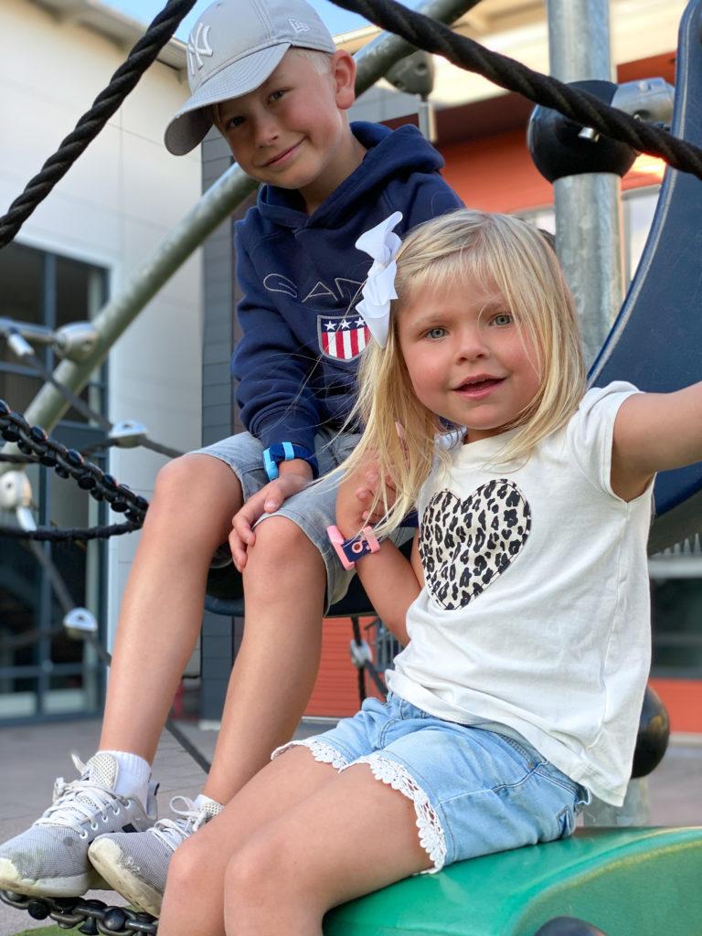 To barn på lekeplass. Gutten til venstre har en blå XPLORA smartklokke, mens jenten til høyre har en rosa XPLORA smartklokke