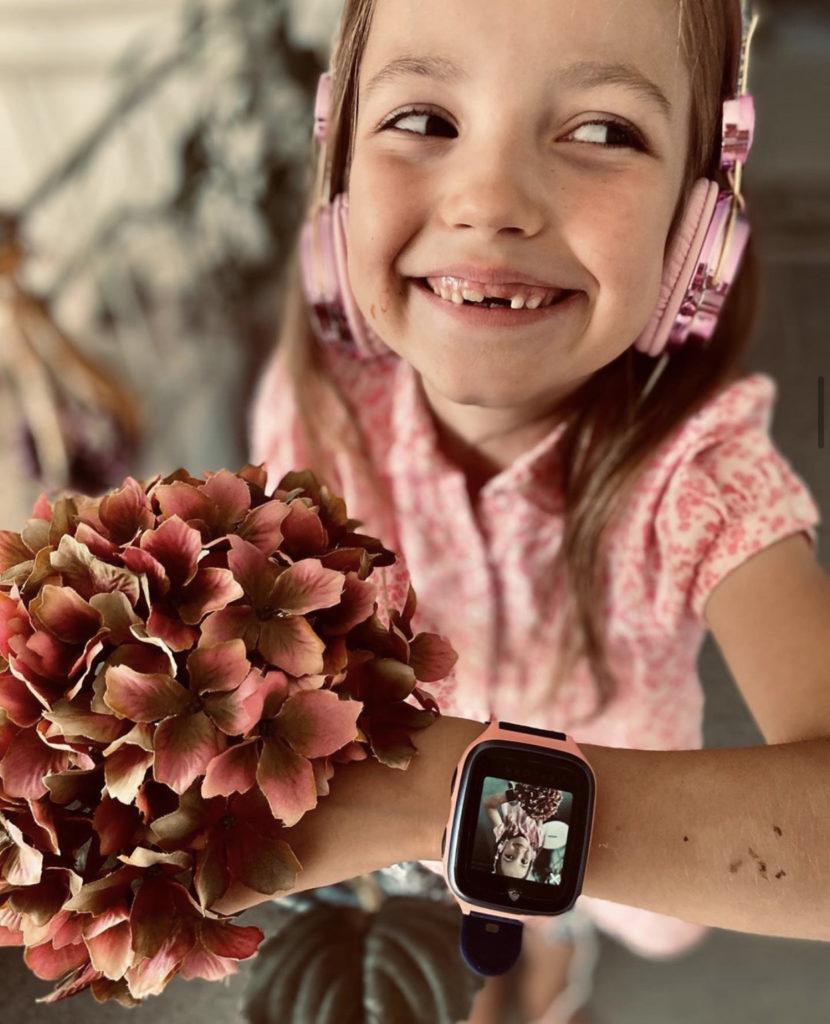 Jente som holder blomster. Hun har en rosa XPLORA-klokke på armen, har rosa kjole og rosa hodetelefoner.