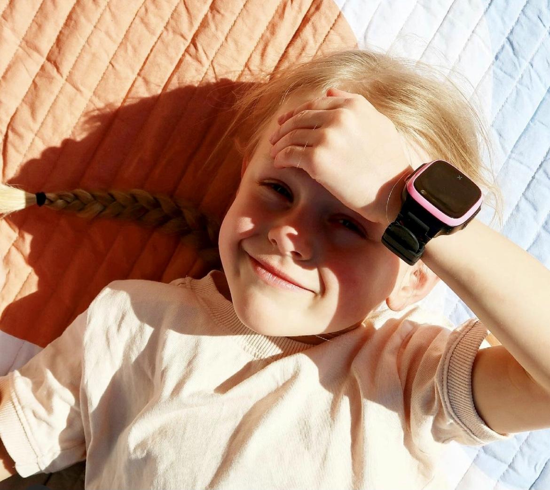 Barn med klokke som ligger i sola